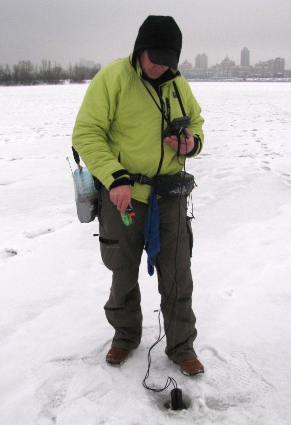 Юрий Орлов опускает в лунку зимний датчик эхолота